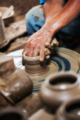 dirty hands making pottery in clay on whee