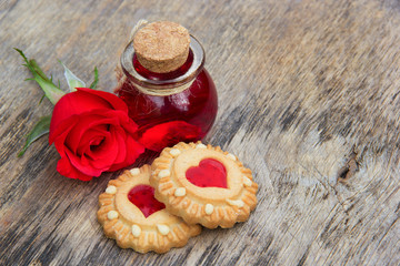 Elixir of Love and cookies in the shape of hearts. Love Potion and fragrant red rose. Romantic concept. Aphrodisiac and massage oil of roses. Romantic set. Copy space.