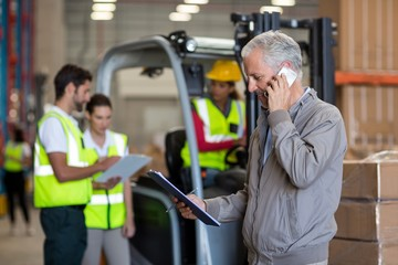 Warehouse manager talking on mobile phone
