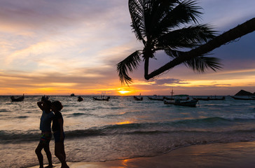 Beautiful sunset by the beach. Silhoette of coconut tree and tourists posing for photo at Tao Island, Thailand. Romantic vacation getaway.