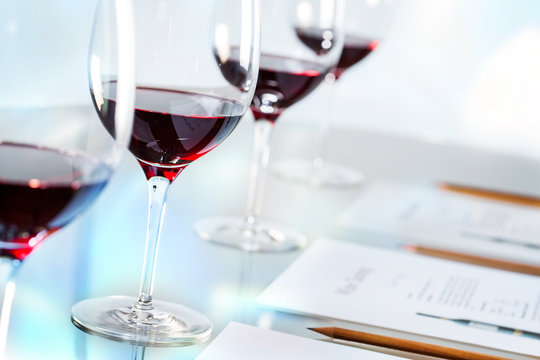 Glasses of red wine on table with pencils and paper.