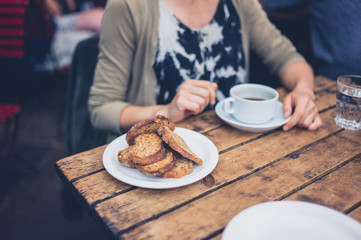 Young woman having coffee and toast
