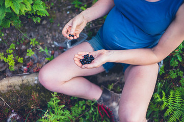 Pregnant woman with black currants in garden