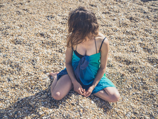 Young woman in sarong sitting on the beach