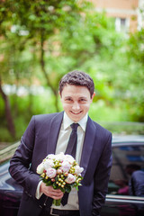 Handsome groom stands with wedding bouquet before a car
