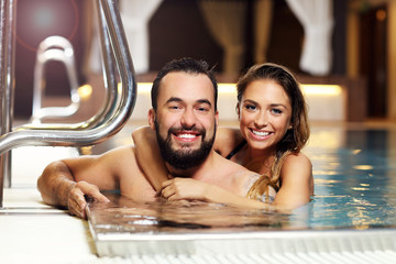 Happy couple relaxing in pool spa