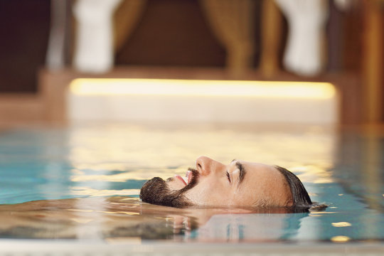 Handsome man relaxing in pool spa