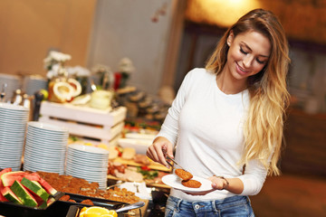 Attractive woman at breakfast buffet in hotel