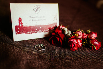 Red roses and wedding rings lie behind an invitation letter on t