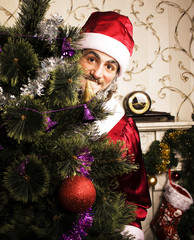 portrait of funny Santa Claus at home with christmass tree close up smiling, lifestyle people concept