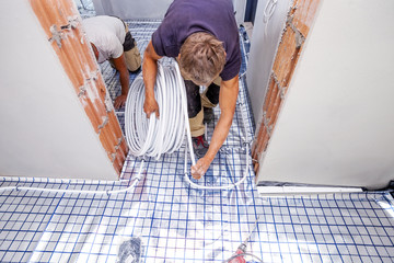 Plumber installs central heating. Pipe fitter mounted underfloor heating. Heating system and underfloor heating.