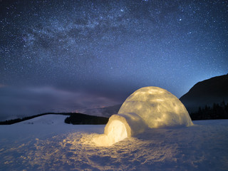 Winter night landscape with a snow igloo and a starry sky