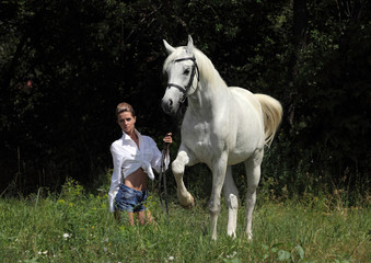 Fashion model with white arabian horse
