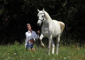 Fashion model with white arabian horse