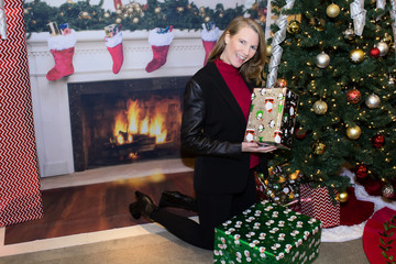 Blonde Female In Front of Fireplace and Christmas Tree Holding Gifts