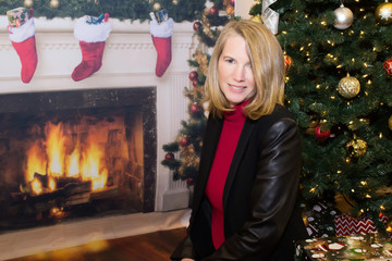 Blonde Female Sitting by Fireplace and Christmas Tree