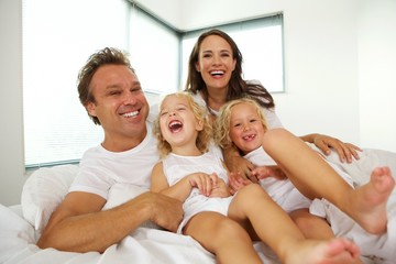 Cheerful young family with children relaxing on bed