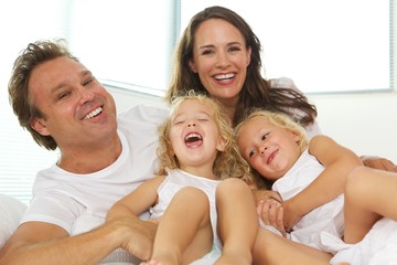 Happy young family of four in bed at home