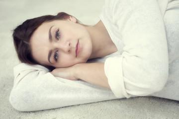 portrait of brunette woman lying on carpet