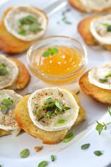 Gebackene Crostini-Partyhäppchen mit Ziegenkäse, frischen Kräutern und Feigenhonig serviert - Baked spicy crostini appetizers with goat cheese and fresh herbs served with fig honey