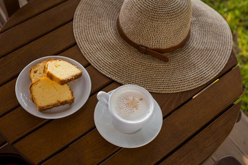 Cup with coffee on table toasts and hat with sunlight. Beauty nature background in the morning on holiday