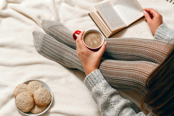 A young woman in a sweater and stockings, with biscuits and red coffee cup in hands relaxing in bed. top view