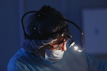 Doctor performing surgery in a dark blue background. Close-up portrait of doctor at work. It makes the operation on his face in a hospital or hospital, breaking his nose. Lantern on his forehead