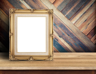 Gold victorian picture frame on plank wooden table top at tropic