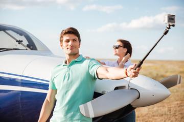 Couple making selfie standing near plane