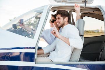 Happy smiling couple making selfie inside plane cabin