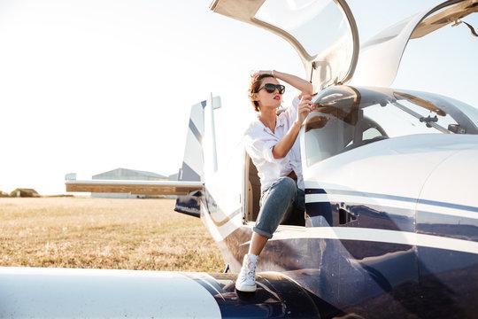 Woman in sunglasses sitting in small private plane