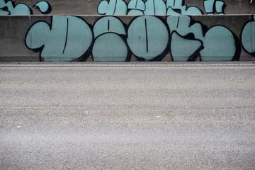 Straßenbaustelle mit Begrenzung / Eine mit Graffiti bemalte Straßenbaustelle mit Fahrbahnbegrenzungen.
