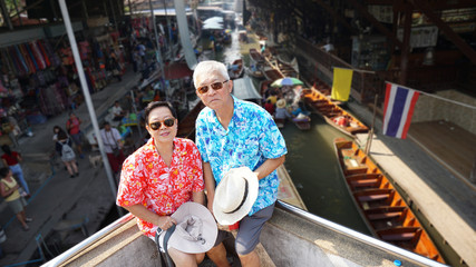 Asian elderly couple having retirment trip to Thailand floating