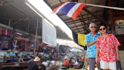 Asian elderly couple having retirment trip to Thailand floating