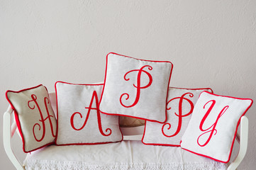 Decorative beautiful pillows with red letters on them making word Happy