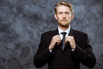 Young successful businessman correcting jacket over grey background.