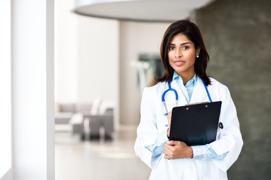 Attractive hispanic latin young woman doctor nurse practitioner in hospital clinic medical office