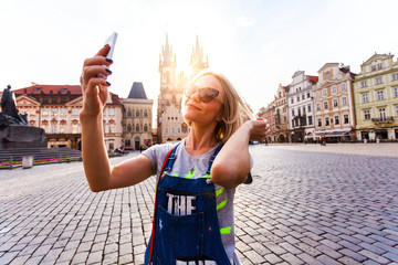 Beautiful young female traveler making self photo on her mobile phone on the background of the Church of Virgin Mary in Old Town Square in Prague. Kostel Panny Marie pred Tynem.