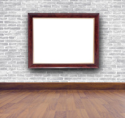 Picture frame on brick wall and wooden floor.