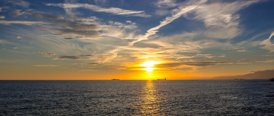 Sunset over the ocean with the boats inside / beautiful landscape sunset