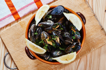 Poster Coquillage Steamed mussels in a pot on the cutting board, tablecloth on wooden table