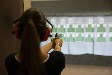 Woman is aiming a gun in the shooting-range