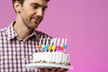 Displeased man holding birthday cake with one not blow out candle.