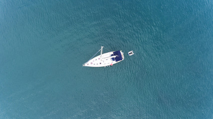 Top view of sailing yacht with a small pontoon floating in the middle of calm sea turquoise, green waters