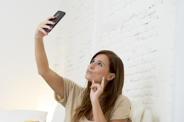 attractive 30 years old woman playing on home sofa couch taking selfie portrait with mobile phone