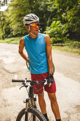 Close up image of young man standing by the  mountain bike on old country road.