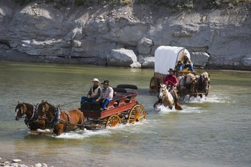 Cowboys And A Chuck Wagon Crossing A River