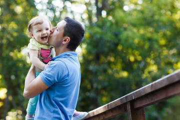 Dad kissing his little daughter on bridge in park