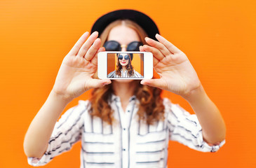 Fashion cool girl taking picture self portrait on smartphone ove