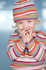 Little Girl In Colorful Hat And Sweater